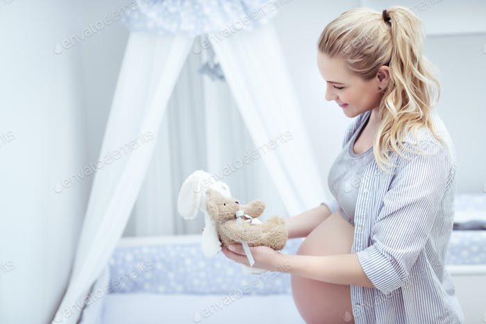 Happy mother prepares child's room