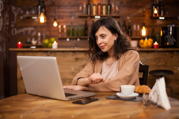 Portrait of smart beautiful woman using laptop for work in a coffee shop
