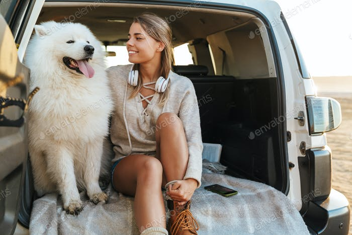 Woman hugging dog samoyed outdoors at the beach in car.