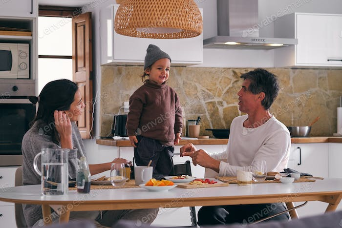 Parents interacting with little daughter in kitchen