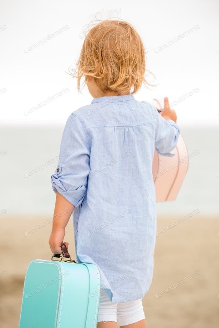 Cute little girl with her suitcase at the sea