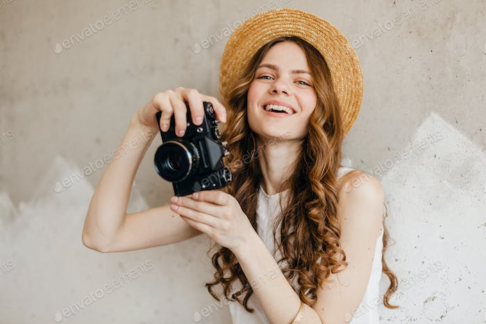 young pretty smiling happy woman in straw hat holding vintage photo camera