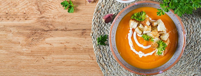 Pumpkin soup in a bowl served with parsley and croutons. Vegan s
