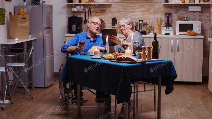 Frau zeigt Tablette zu gelähmten Mann