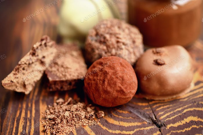 Handmade chocolate candies and pieces of chocolate on wooden bac