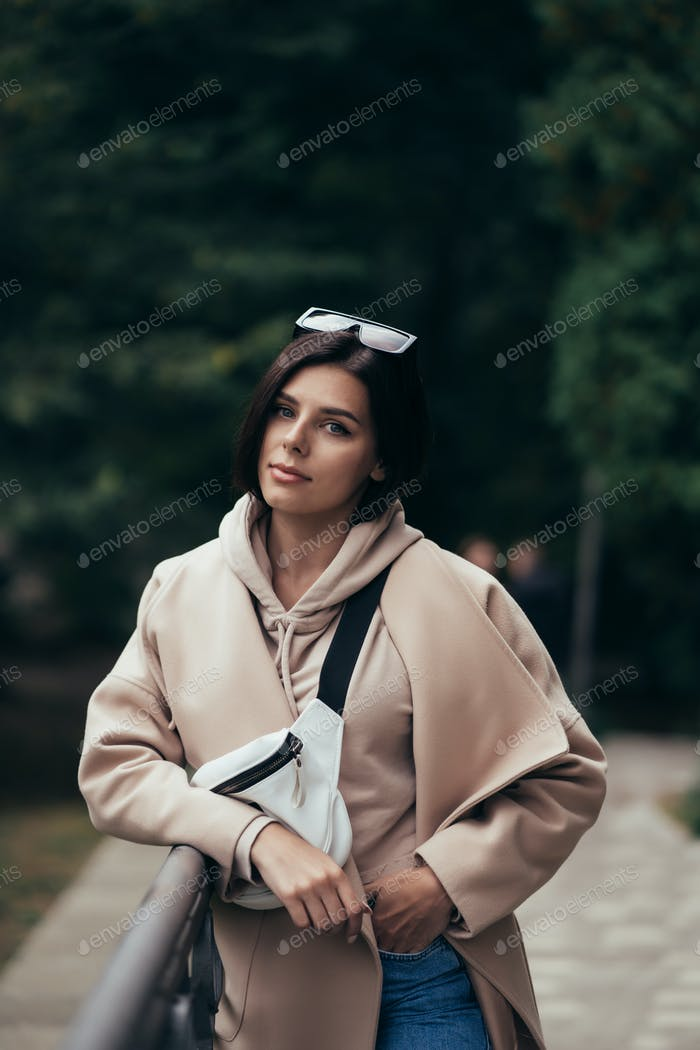 Closeup portrait of beautiful fashionable woman in park