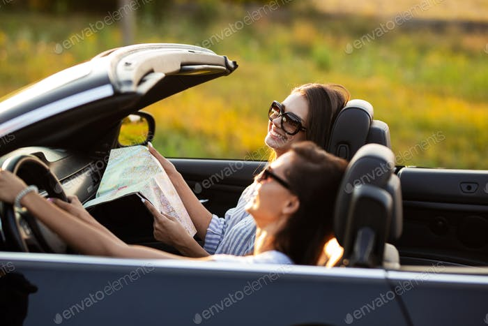 Two beautiful young women in sunglasses are sitting in a black cabriolet and smiling on a sunny day