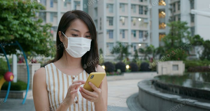 Woman wear face mask and use of mobile phone at street
