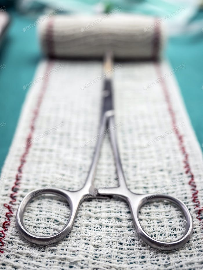 Surgical scissors on a bandage, conceptual image