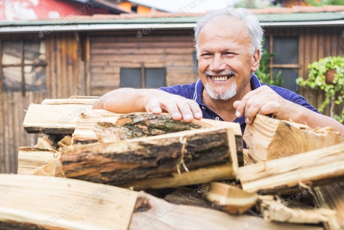 aged senior man smile and prepare the wood for the winter heating