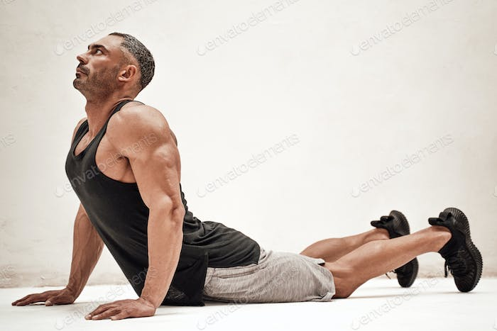Strong and muscular athlete posing in a bright studio while doing a lion yoga pose