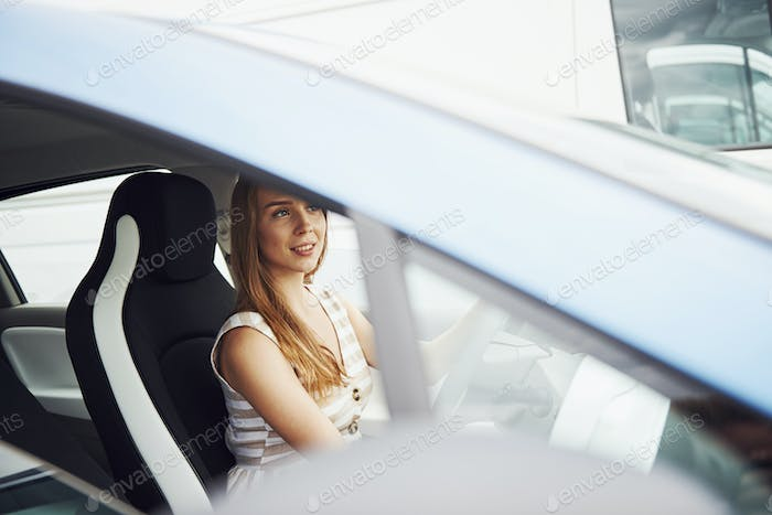 Female driver inside of modern automobile. Testing brand new car