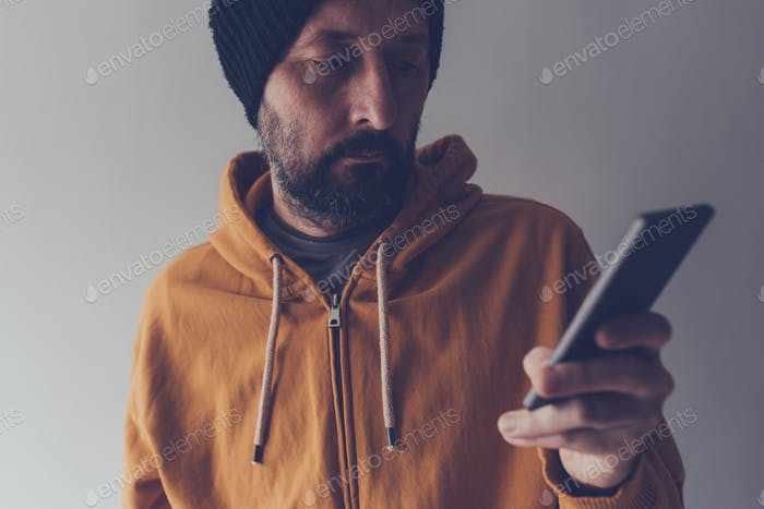 Casual adult male with cap looking at mobile phone