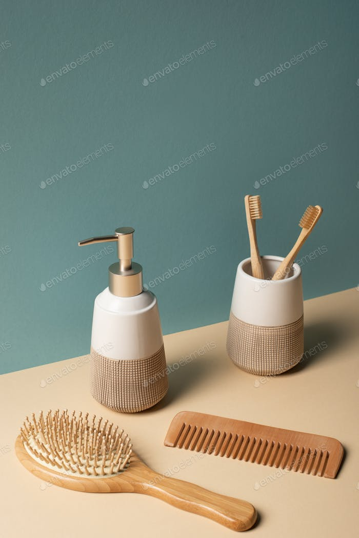 Toothbrushes, comb, liquid soap dispenser on beige and grey, zero waste concept