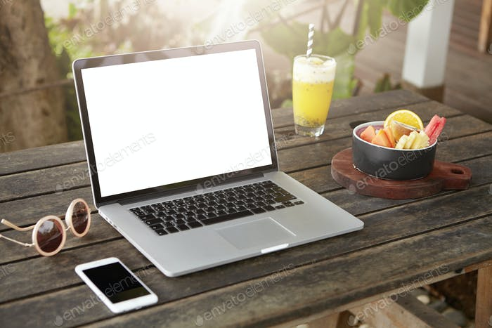 Technology, business and communication concept. Workspace with modern open laptop, mobile phone and