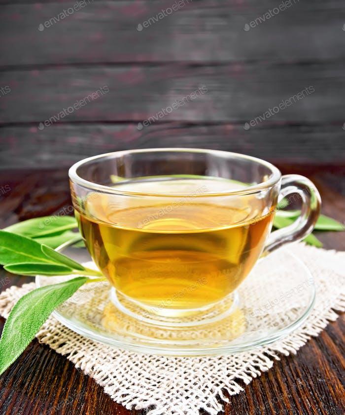 Tee-Kräuter mit Salbei in Glasbecher auf Holzbrett