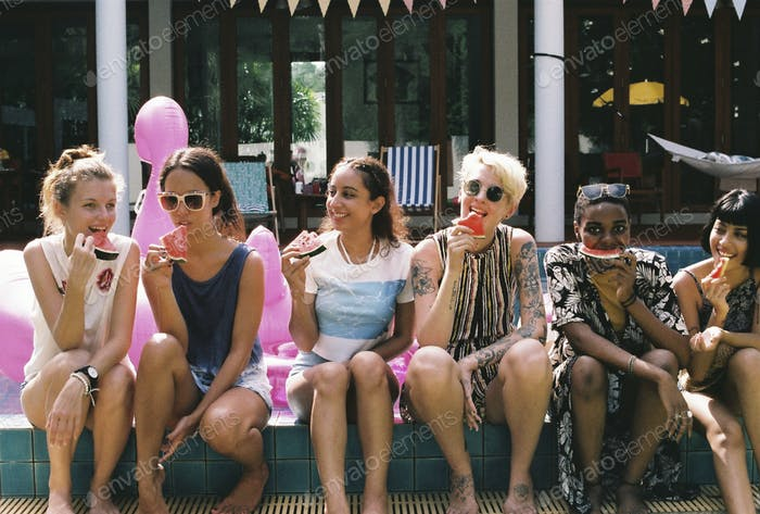Group of girls friends eating watermelon at the pool