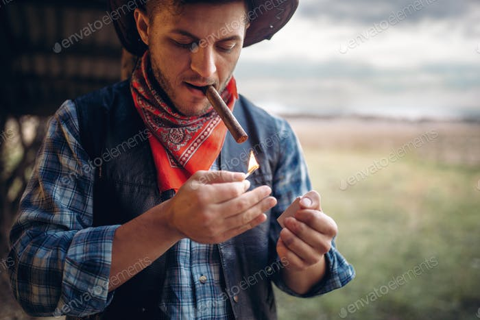 Bearded cowboy lights a cigar, wild west culture