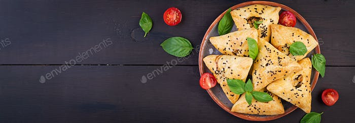 Asian food. Samsa (samosa) with chicken fillet and green herbs on wooden background. Banner