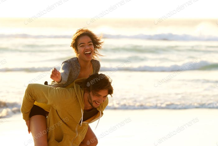 Young man carrying smiling woman on back at the beach
