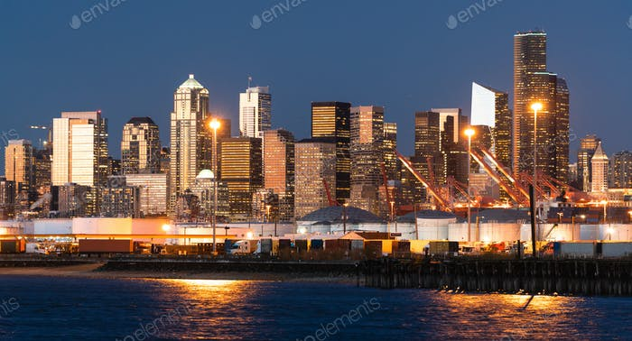 The Seattle Washington waterfront glows at dusk showing tanks on the port