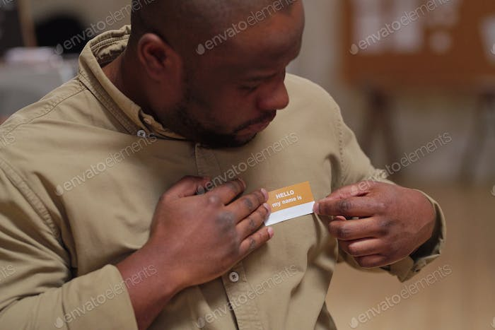 Middle aged man of African ethnicity putting badge with his name on chest and looking at it