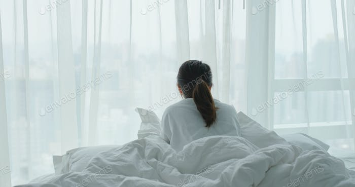 Woman lay down on bed and look outside the window