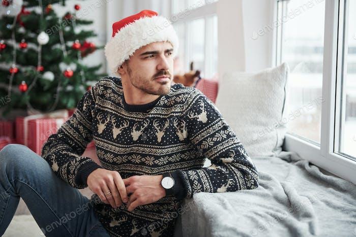 Foto von Mann mit Weihnachtsmütze und Feiertagskleidung schaut durch das Fenster