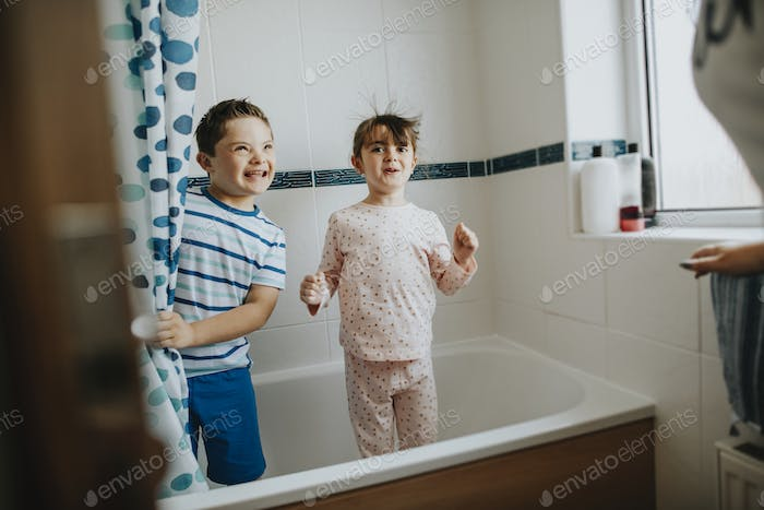 Sister and brother playing peekaboo in the bathroom