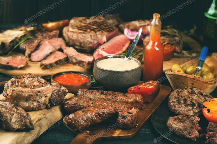 Assorted delicious grilled meat with vegetables on dark table