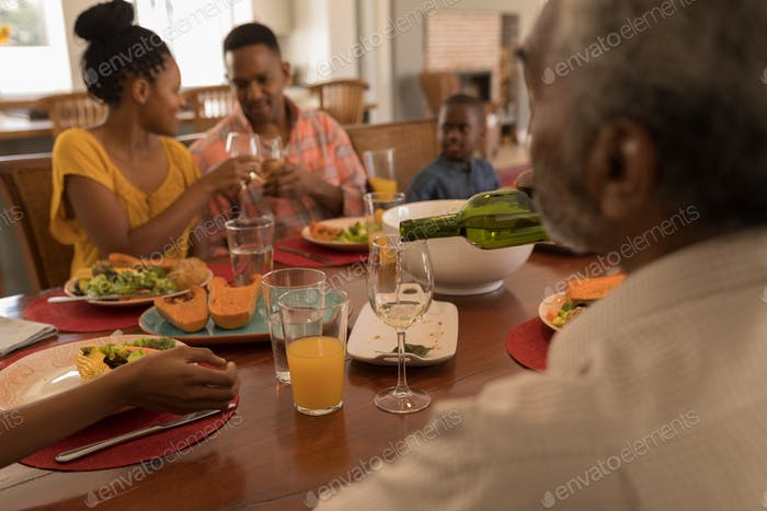 Rear view of a multi-generation family having wine on dining table at home