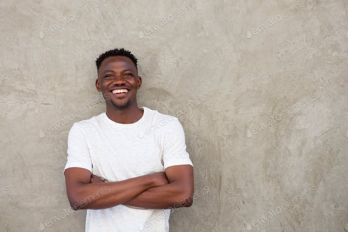 handsome young african man smiling with arms crossed by wall
