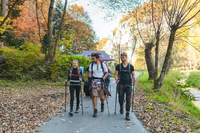 Friends with backpacks walking outdoor together, trekking and tourism