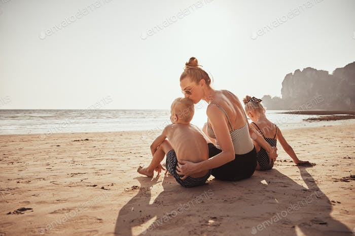 Loving Mother sitting with her children on a sandy beach