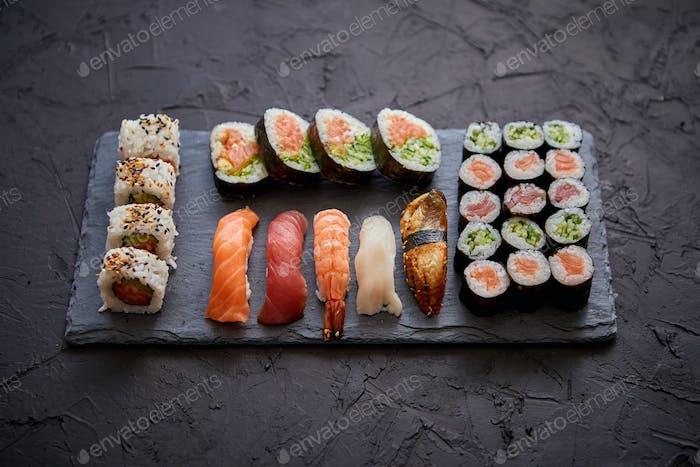 Sushi-Brötchen Set mit Lachs und Thunfisch serviert auf schwarzem Steinbrett