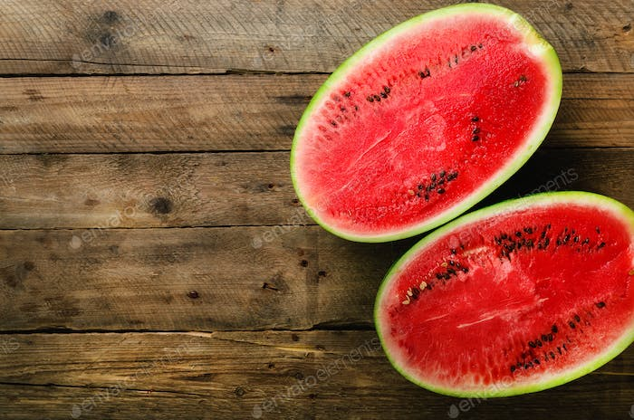 Tasty organic watermelon cut in half on wooden background with copy space
