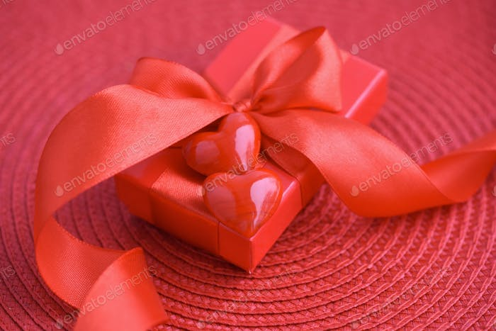 Valentines Day background. Hearts with red gift box on red backg