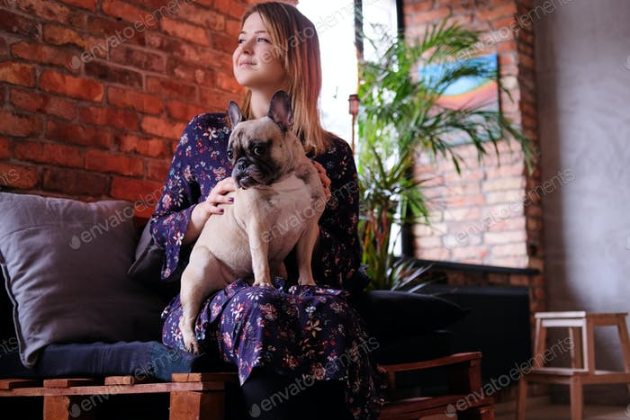 Glückliche blonde Frau im Kleid sitzt mit ihrem niedlichen Mops auf einem handgefertigten Sofa im Zimmer mit Loft-Interieur.
