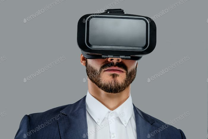 A man in a suit with virtual reality glasses on his head.