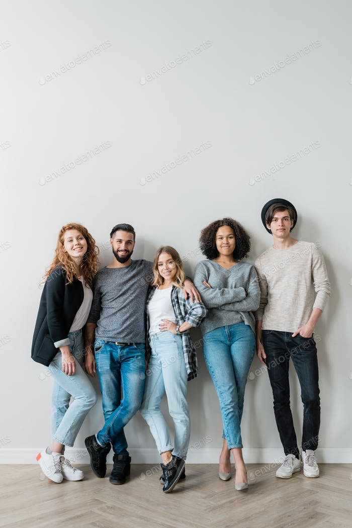 Group of cheerful young affectionate friends in jeans and pullovers