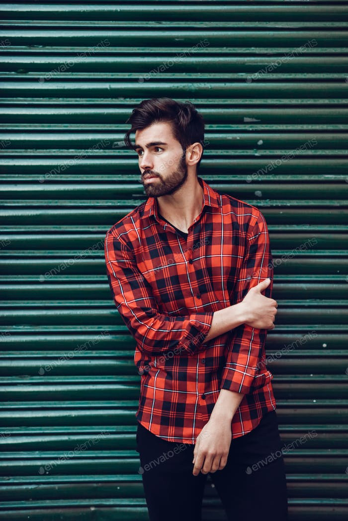 Young bearded man, model of fashion, wearing a plaid shirt with a green blind behind him.
