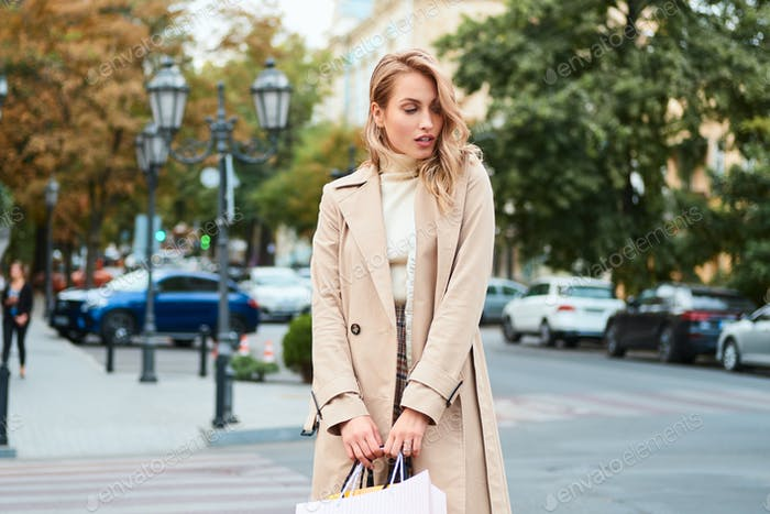 Beautiful casual blond girl in stylish trench coat with shopping bags standing on city street