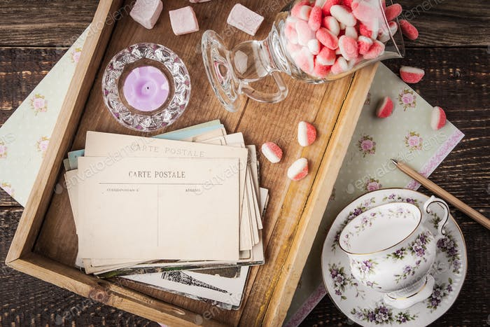 Tea things with sweets and postcards on the wooden tray top view