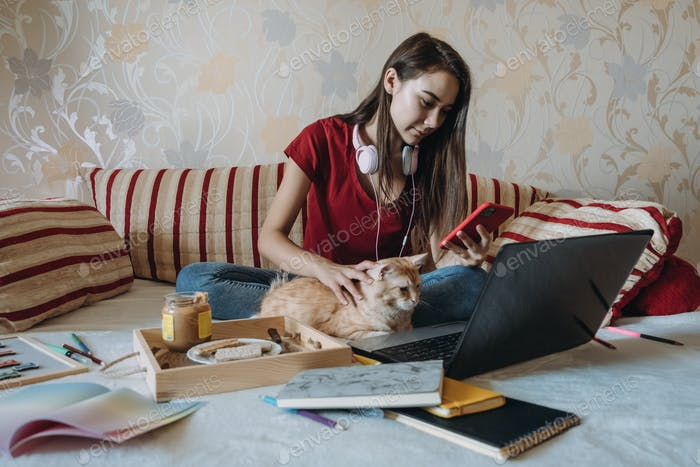 Freelance young woman working in home office with laptop computer and cat. Remote online working