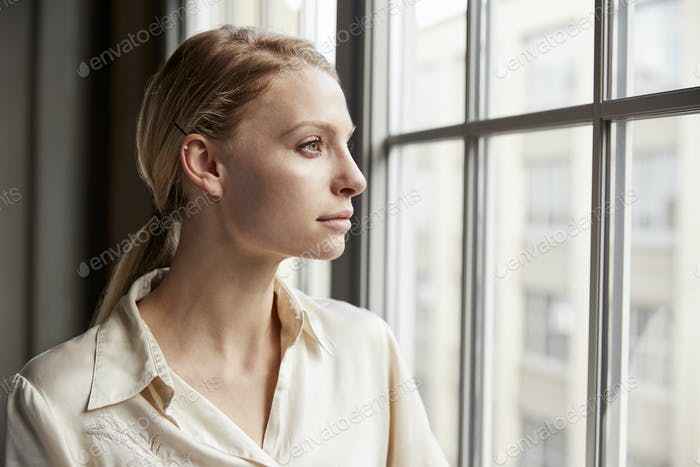 Young blonde businesswoman looking out of window