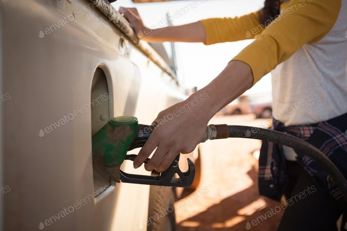 Frau füllt Benzin im Auto an der Benzinpumpe