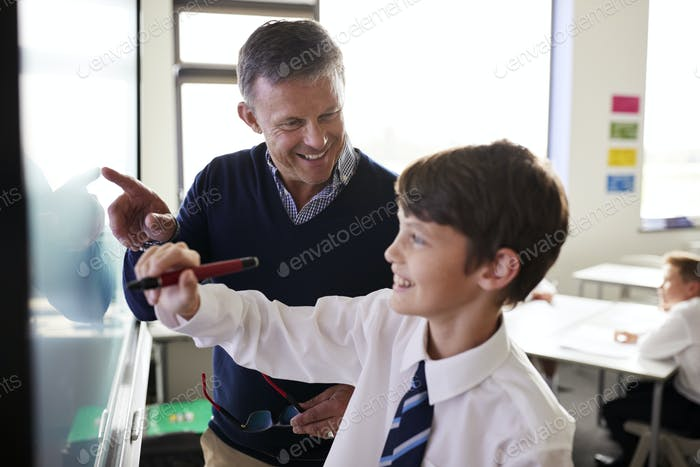 High School Teacher With Male Student Wearing Uniform Using Interactive Whiteboard During Lesson