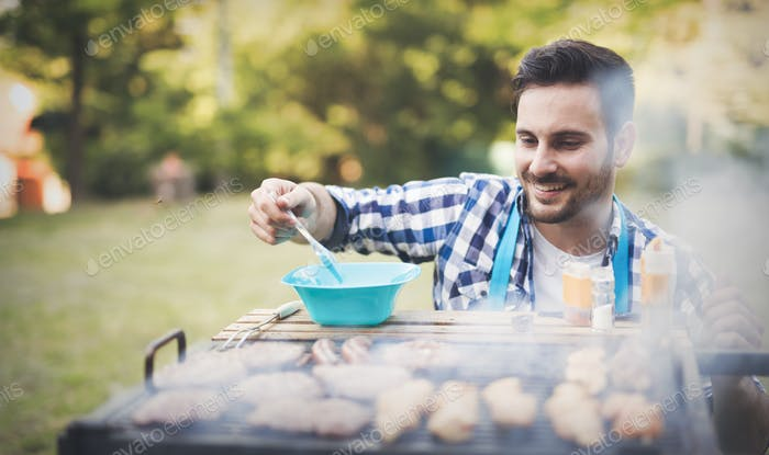 Handsome male grilling meat outdoor