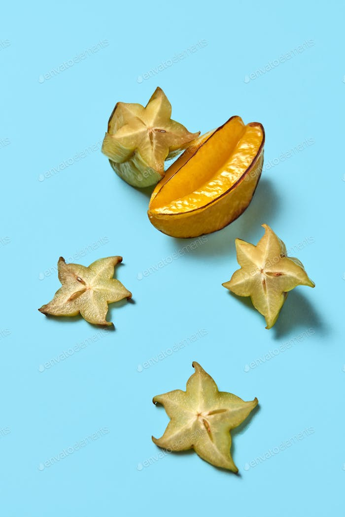 Ripe tropical fruit of a carambola sliced pieces presented on a blue background with copy space