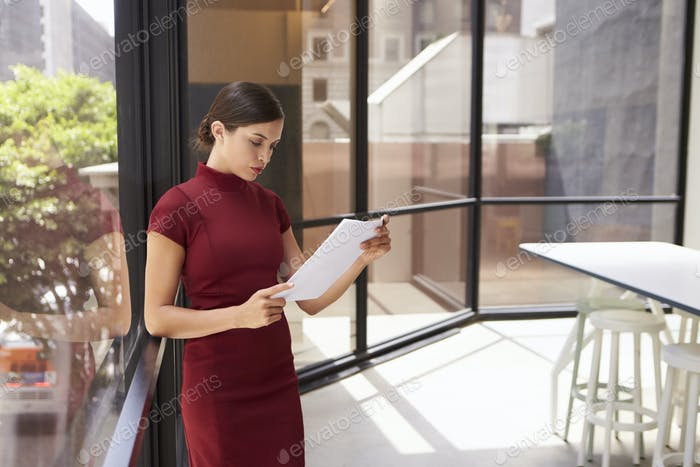 Young white businesswoman reading document in modern office